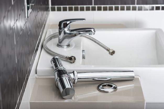 浴室の新しい金属サイフォンおよび他の流し設備。 Premium写真