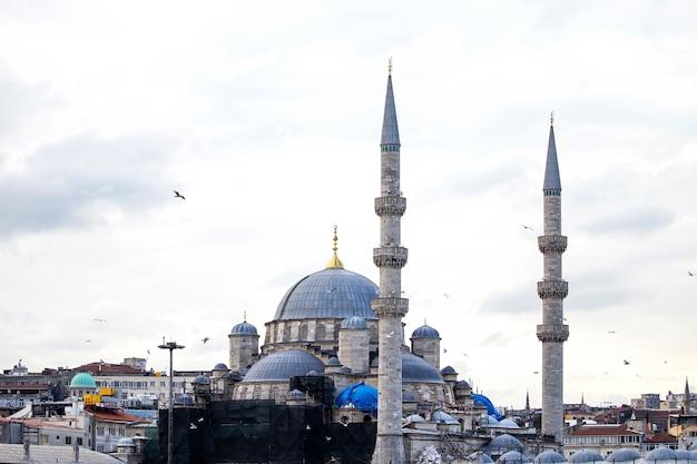 Nuova moschea di istanbul a tempo nuvoloso con edifici residenziali intorno e uccelli in volo, turchia Foto Gratuite