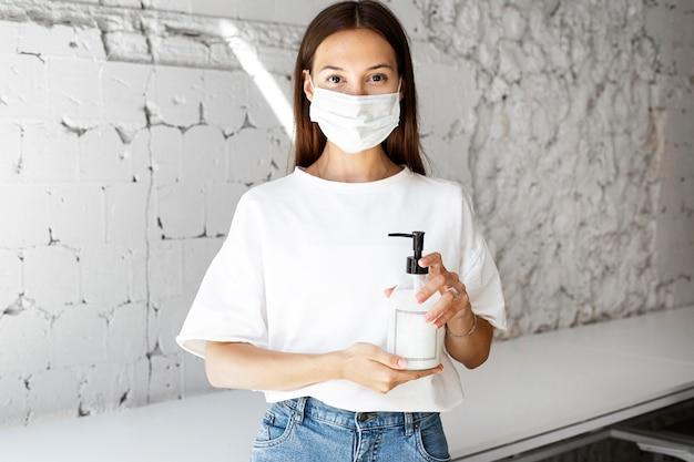 Новый нормал в офисе с маской для лица и дезинфицирующим средством Бесплатные Фотографии