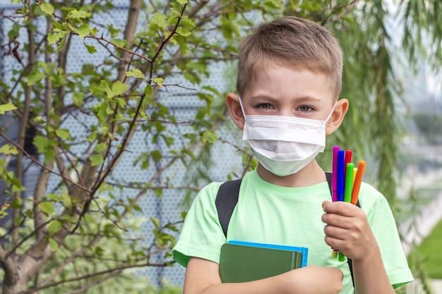 新しい通常、学校に戻って。医療マスクと教科書とフェルトペンを屋外で保持しているバックパックを身に着けている少年 Premium写真