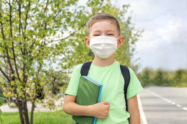 新しい通常、学校に戻って。医療マスクと屋外で教科書を保持しているバックパックを身に着けている少年 Premium写真