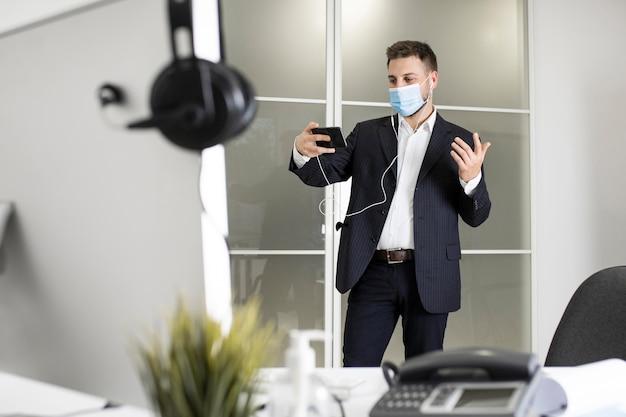 Nuovo normale in ufficio con maschera facciale Foto Gratuite