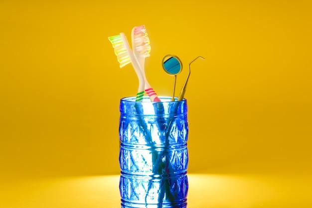 Новые пластиковые зубные щетки внутри стекла, изолированные на ярко-оранжевый Premium Фотографии