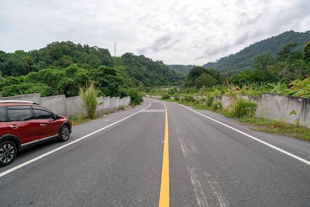 山の緑の森とアスファルト道路上の新しい赤いsuv車 Premium写真