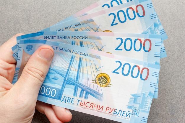 Новые российские банкноты номиналом 2000 рублей в мужской руке крупным планом Premium Фотографии