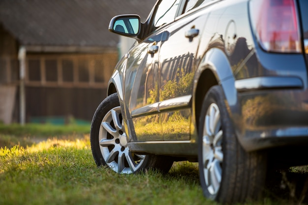 Новый блестящий серый автомобиль припаркован на зеленой траве на размытом солнечном летнем сельском фоне. Premium Фотографии