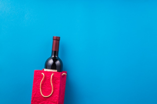 New wine bottle in red paper bag against blue backdrop Free Photo