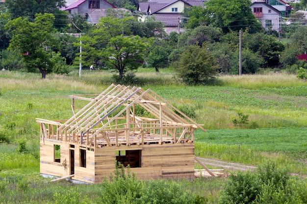 緑の近所で建設中の急な板の屋根フレームを備えた天然木材の新しい木造コテージ。プロパティ、投資、専門的な建物と再建のコンセプト。 Premium写真