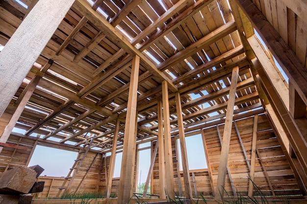 建設中の新しい木造住宅。内側から窓が開く壁と天井フレームの拡大図。自然素材の生態学的夢の家。建物、建設、改修のコンセプトです。 Premium写真