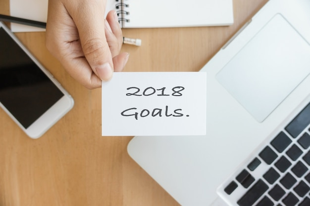 New year 2018 - closeup top view photo woman showing 2018 goal list on business card and using modern laptop and mobile phone on wood table blurred background. Free Photo