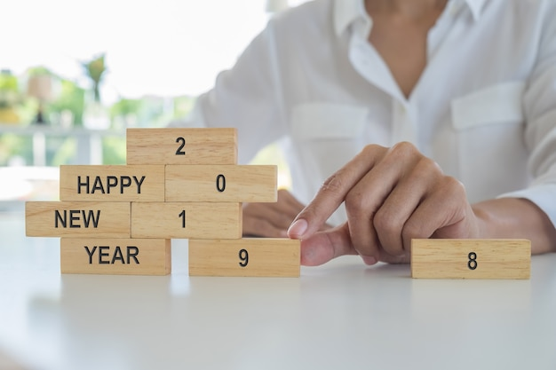 New year 2019 concept. young woman building 2019 concept with wooden blocks. Premium Photo