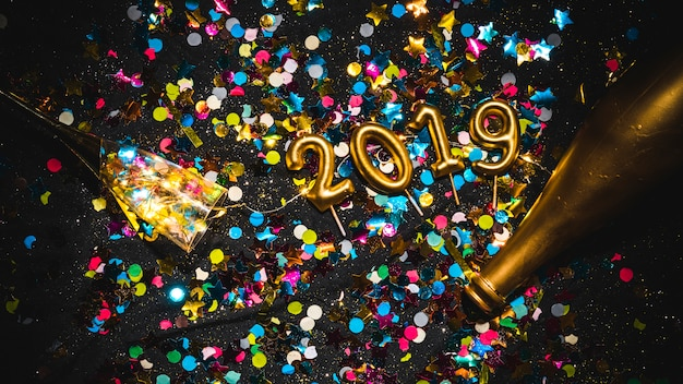 New year 2019 shaped candles on confetti stack Free Photo