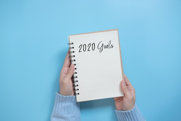 New year 2020 goals list with notebook on blue background, flat lay style. planning concept. Premium Photo