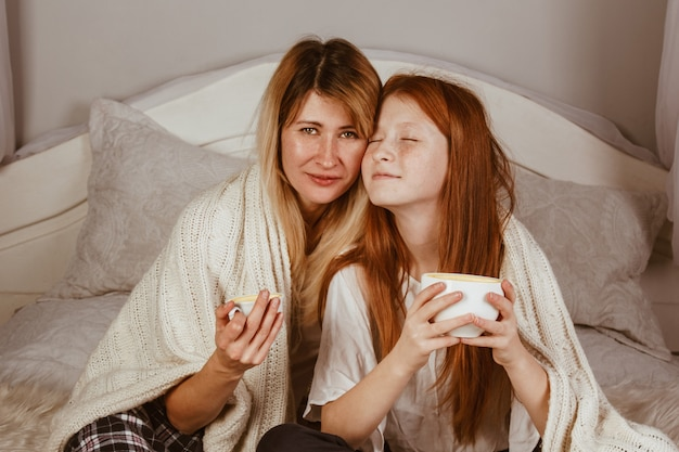 New year 2020. mom and ginger-haired daughter are sitting on the bed and drinking cocoa with froth. covered with a blanket, hug. Premium Photo