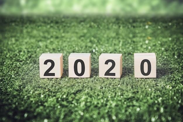 緑の背景を持つ木製キューブの新年2020。 Premium写真