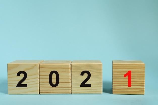 새 해 2021 개념, 파란색 배경에 번호와 나무 큐브. 디자인 목업 프리미엄 사진