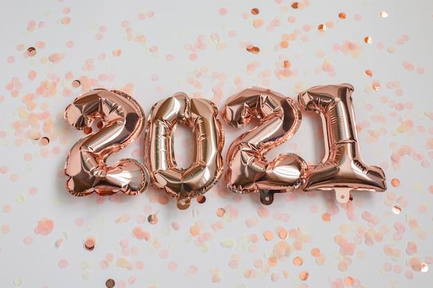 Концепция празднования нового года и рождества 2021 года. воздушные шары из фольги в виде цифр 2021 и конфетти на розовом фоне. воздушные шары. украшение праздничной вечеринки. Premium Фотографии