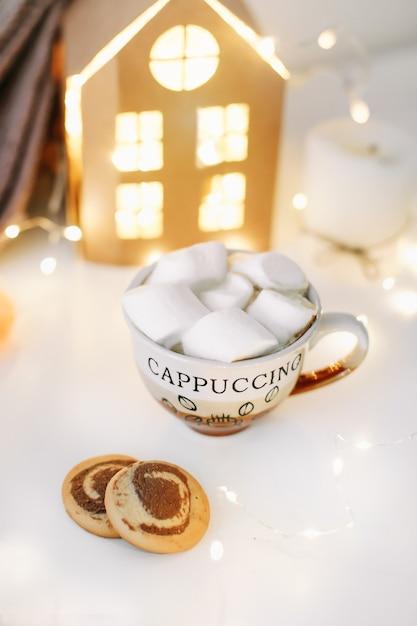 Новогодний и рождественский фон с чашкой кофе с зефиром и свечами на белом Premium Фотографии