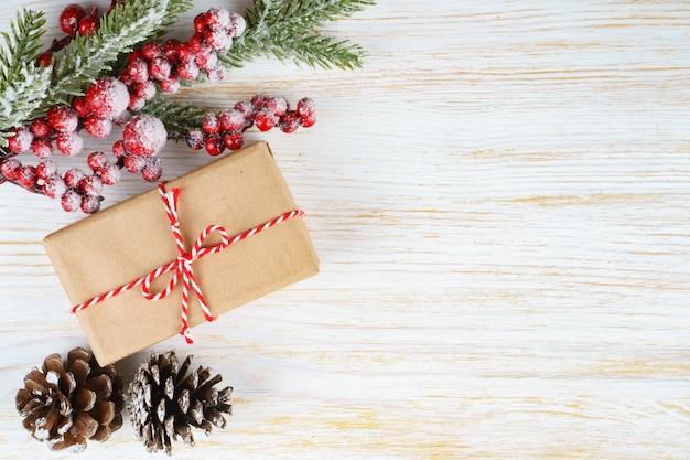 Новогодний фон с веткой рождественской елки, декоративной елью, еловыми шишками и подарочной коробкой на белом деревянном фоне с пространством для текста. плоская планировка, вид сверху. Premium Фотографии