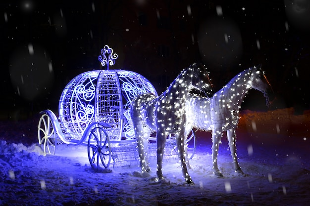 New year card. luminous figure of horses with a carriage. snow, night. place for text Premium Photo
