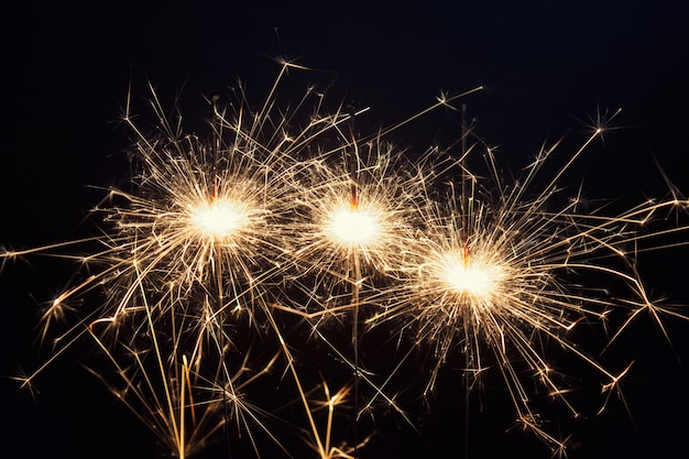 New year celebration greeting card with three burning sparklers with spiky flames Premium Photo