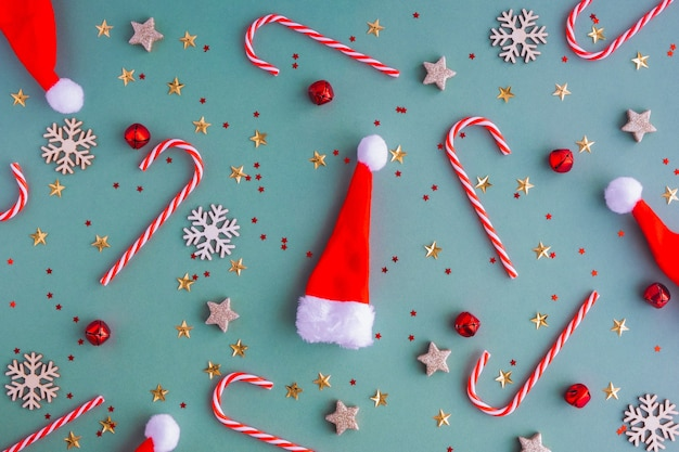 New year or christmas background. flat lei from santa claus hats and christmas toys and lollipops Premium Photo