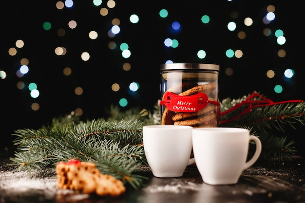 New year and christmas decor. bottle with chocolate cookies and cups for tea Free Photo