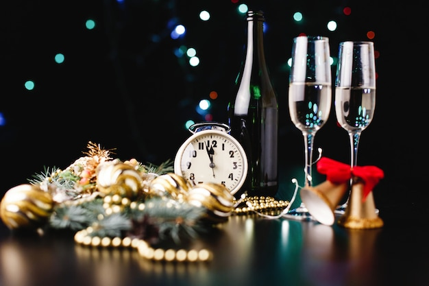 New year and christmas decor. glasses for champagne, clock and toys for christmas tree Free Photo