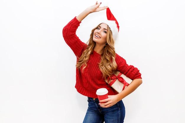 New year or christmas eve mood. blond attractive girl in masquerade hat holding gift boxes isolate Free Photo