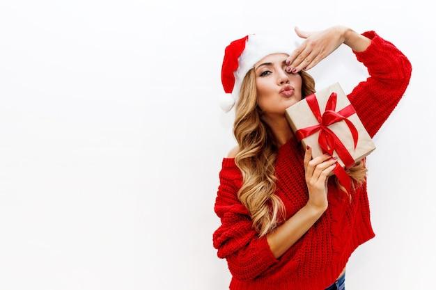 Umore del nuovo anno o della vigilia di natale. ragazza attraente bionda nel cappello mascherato che tiene i contenitori di regalo stato d'animo gioioso. Foto Gratuite