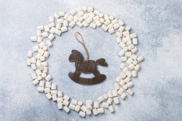 New year or christmas flat lay top view with marshmallows and rustic wooden horse toy Premium Photo