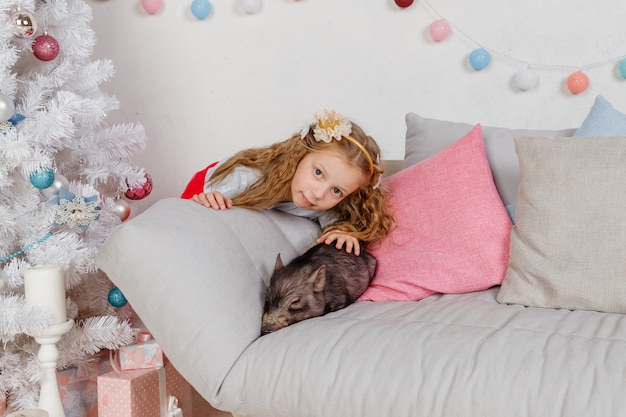 New year and christmas. girl in festive clothing and mini pig. pig symbol of 2019. black pig. chinese horoscope. friendship and care for the younger Premium Photo