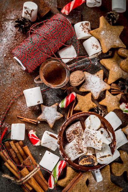 新年、クリスマスのお菓子、お菓子。揚げマシュマロ、ジンジャースタークッキー、ジンジャーブレッド男性、縞模様のキャンディ、スパイスシナモンアニス、ココア、粉砂糖入りのホットチョコレートのカップ。コピースペーストップビュー Premium写真