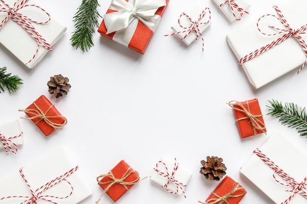 Новогодняя композиция. поверхность рождества с красными и белыми обернутыми подарочными коробками с лентой, еловыми ветками, шишками на белой поверхности, копией пространства. зимний праздник шаблон. вид сверху, плоская планировка. Premium Фотографии