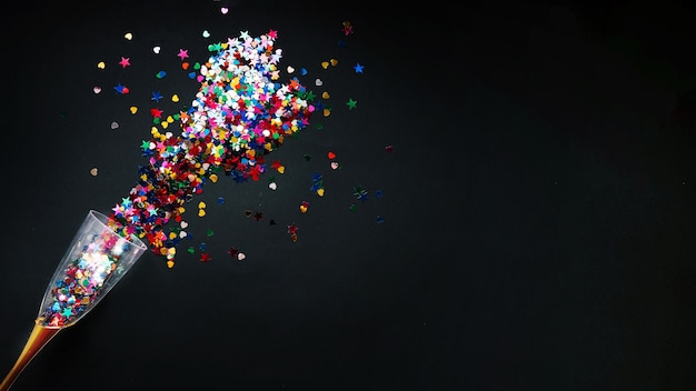 New year composition with colorful confetti in glass Premium Photo