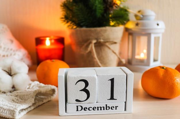 木製のカレンダーキャンドルで新年の構成クリスマスツリーカレンダーニットセータータンジェリン Premium写真