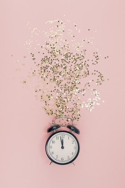 New year concept. alarm clock with golden confetti Premium Photo