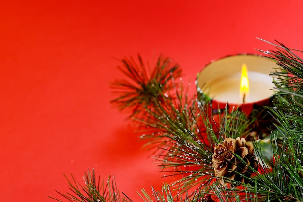 New year copyspace card. christmas tree fir branch, burning candle, decorations, on red background Premium Photo