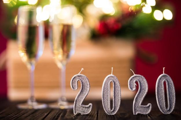 Decorazione di capodanno. due gobelts con champagne con decorazioni di natale o capodanno 2020 su sfondo a luci rosse Foto Gratuite