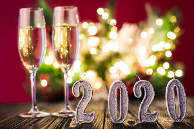 Новогоднее украшение. два гобелена с шампанским с украшением рождества или нового 2020 года на фоне красного света Бесплатные Фотографии