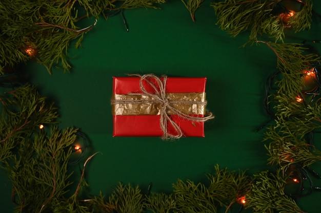 Новогодний подарок на темно-зеленом фоне рождества. Premium Фотографии