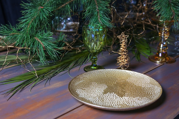 年末年始は金色のプレートでテーブルを飾りました。クリスマスツリーとヴィンテージの青いテーブルの上のヴィンテージワイングラス。 Premium写真