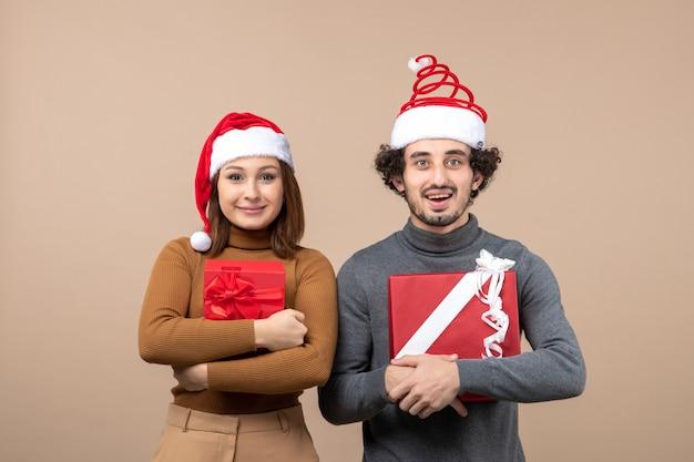 Новогоднее настроение и концепция вечеринки - молодая взволнованная милая пара в шляпах санта-клауса на сером Бесплатные Фотографии
