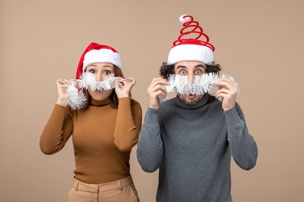 Concetto festivo di umore del nuovo anno con le coppie adorabili soddisfatte fresche eccitate che portano i cappelli rossi del babbo natale sull'immagine di riserva grigia Foto Gratuite