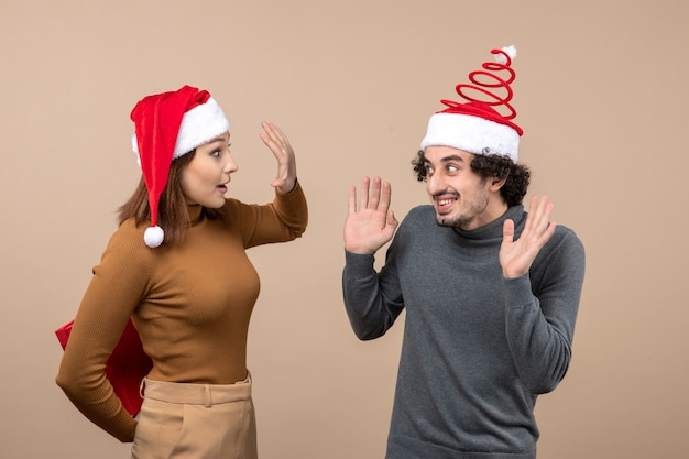 Concetto festivo di umore del nuovo anno con coppia adorabile divertente che porta il regalo nascosto della ragazza dei cappelli di babbo natale rosso dietro su gray Foto Gratuite