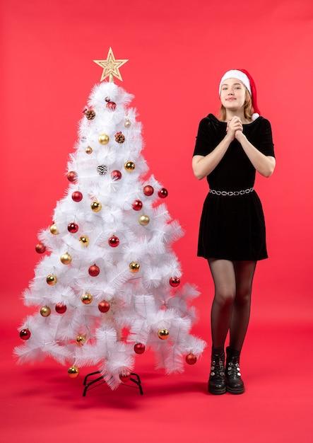 Новогоднее настроение с молодой женщиной в черном платье и шляпе санта-клауса, стоящей возле белой елки Бесплатные Фотографии
