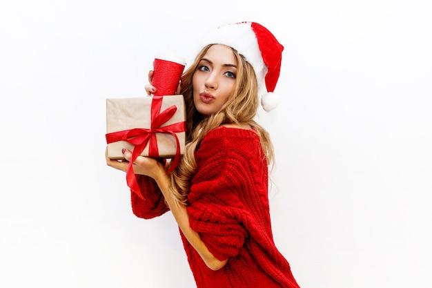 새해 또는 크리스마스 이브 분위기. 선물 상자를 들고 가장 무도회 모자에 금발의 매력적인 여자 분리 무료 사진