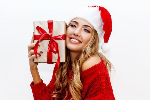 새해 또는 크리스마스 이브 분위기. 선물 상자를 들고 가장 무도회 모자에 금발 매력적인 여자 즐거운 분위기입니다. 무료 사진