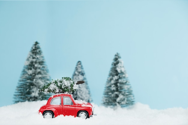 New year red car with christmas tree in snowy forest. happy new year card Premium Photo