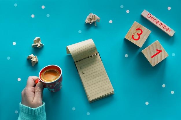 Концепция резолюций нового года, рука с кофе, ноутбук, деревянный календарь и кофе на синем Premium Фотографии